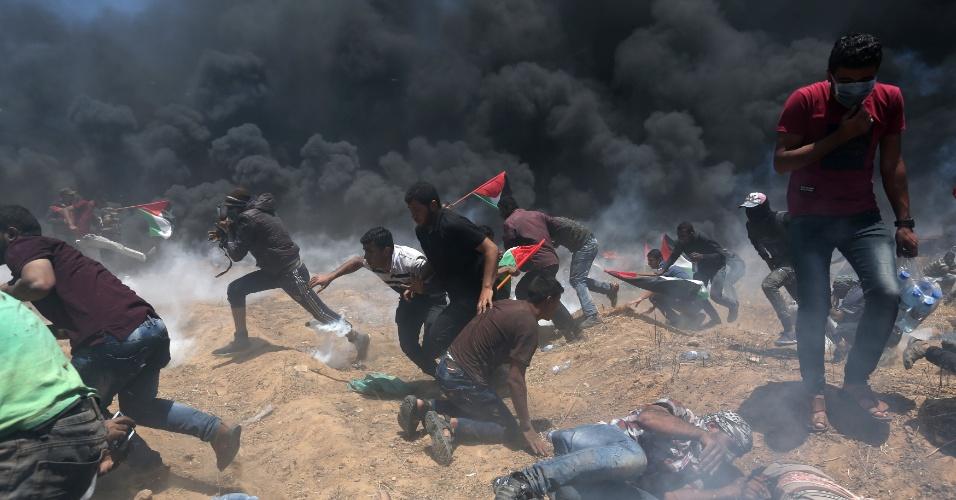 14.mai.2018 - Manifestantes palestinos correm de bombas de gás lançadas por forças israelenses durante protestos contra a inauguração da embaixada dos EUA em Jerusalém