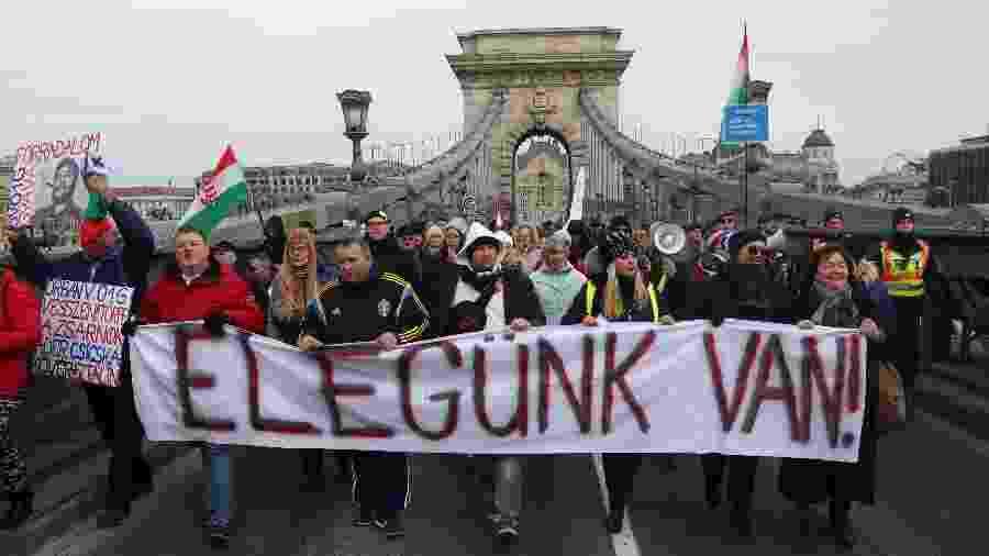 """19.jan.2019 - Manifestantes carregam faixa onde se lê """"Basta!"""" enquanto atravessam a ponte mais antiga de Budapeste, na Hungria, durante protesto contra a política de governo do premiê Viktor Orban para a reforma trabalhista - Ferenc Isza/AFP"""