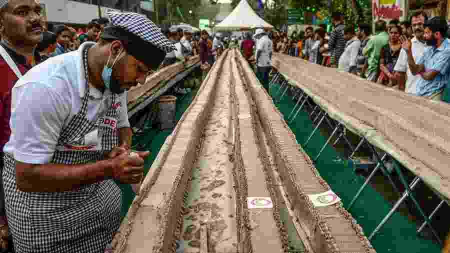 Na Índia, padeiros tentam bater recorde de maior bolo do mundo ao prepararem receita com 6,5 km do doce - Arun Sankar/AFP