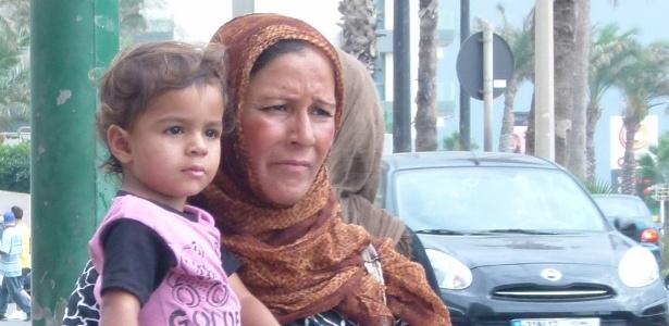 Mulher síria pede esmolas com criança de colo em avenida à beira do mar Mediterrâneo de Beirute