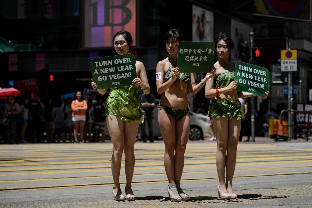 23.jun.2016 - Três mulheres se vestem com roupas feitas de alface e caminham por Hong Kong, na China, durante um protesto pró-vegetarianismo apoiado pelo PETA , organização de defesa aos animais
