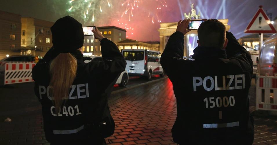 31.dez.2016 - Policias tiram fotos do show de fogos durante as celebrações do Ano-Novo em Berlim, na Alemanha
