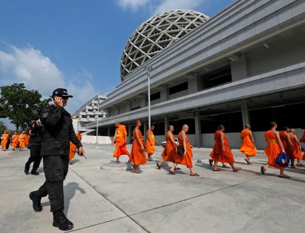 Oficiais do Departamento de Investigações Especiais caminha pela área do templo Wat Phra Dhammakaya durante inspeção, na Tailândia