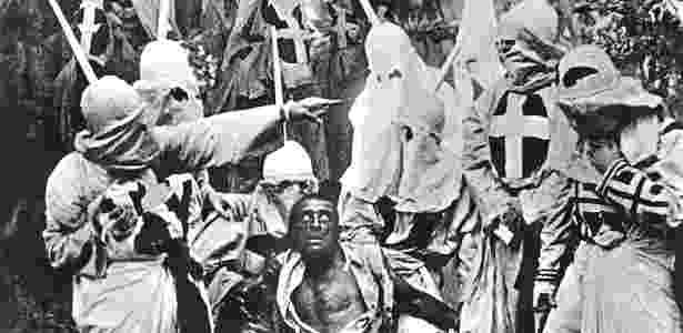 """Atores vestidos como membros da Ku Klux Klan em volta de um ator branco com pele pintada de negro em imagem de """"O Nascimento de uma Nação"""" - Getty Images - Getty Images"""