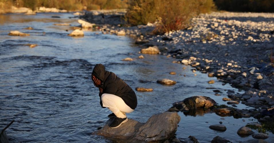 Imigrante lava o rosto antes de tentar cruzar os Alpes para a França