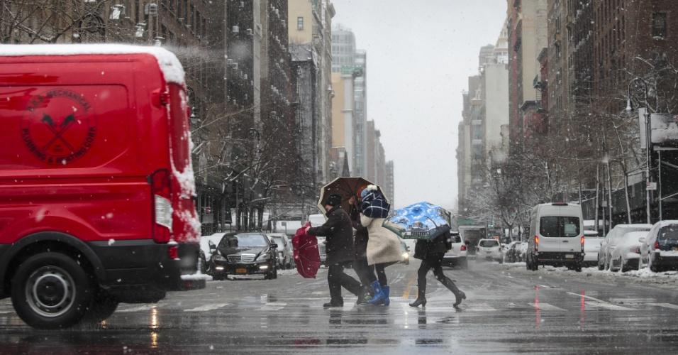 21.mar.2018 - Pedestres atravessam a rua durante tempestade de neve na cidade de Nova York