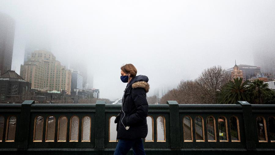 Pessoa de máscara em ponte de Melbourne, na Austrália - STRINGER