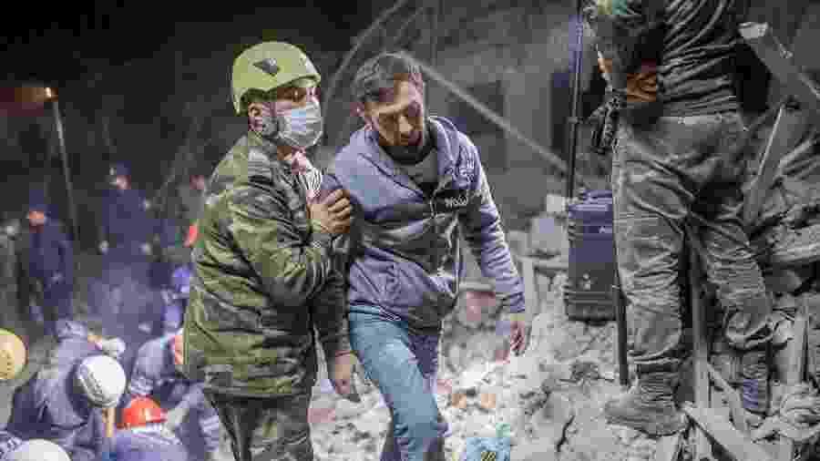 Socorrista ajuda morador na busca por parentes após míssil atingir área residencial no Azerbaijão - Bulent Kilic/AFP