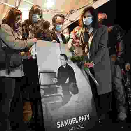 20.out.2020 - Parentes e amigos seguram uma foto do professor Samuel Paty em homenagem em Conflans-Sainte-Honorine; ele foi decapitado em um atentado que chocou a França - Bertrand Guay/AFP