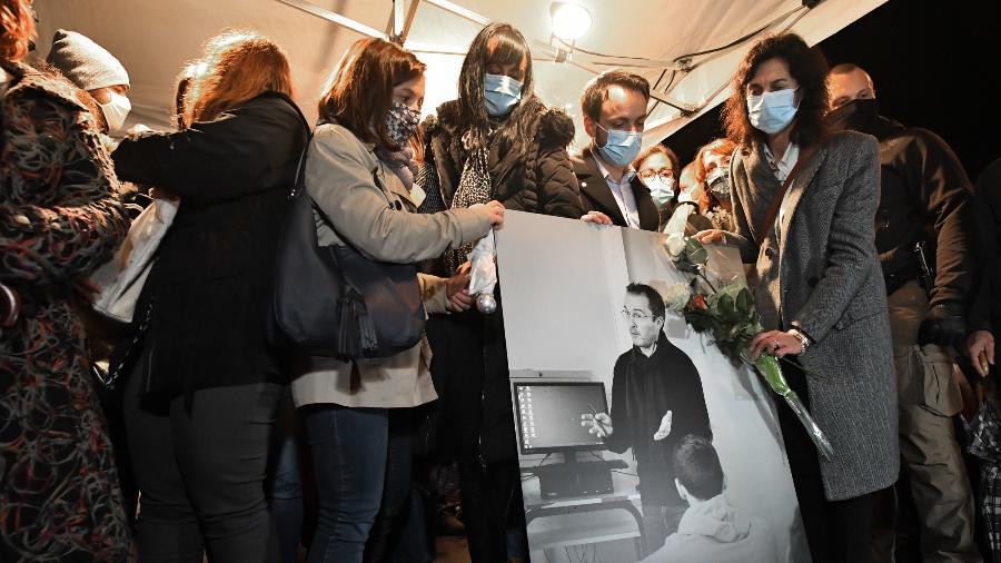 20.out.2020 - Parentes e amigos seguram uma foto do professor Samuel Paty; ele foi decapitado em um atentado que chocou a França - Bertrand Guay/AFP