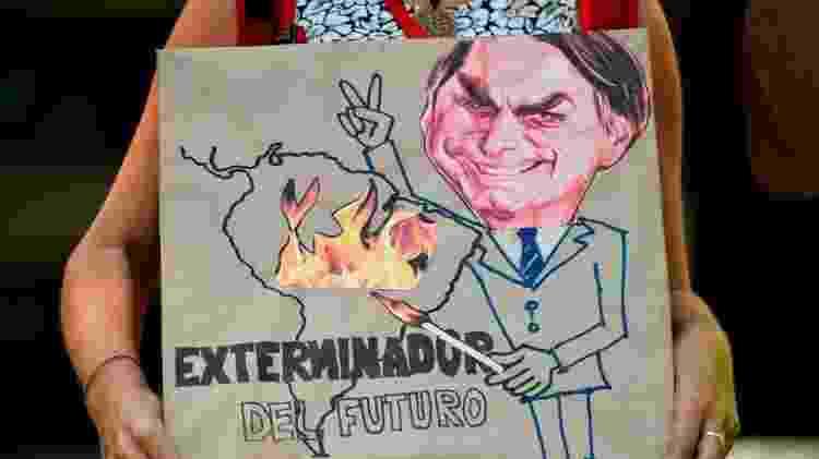 'Exterminador do futuro', diz cartaz que mostra Bolsonaro com um palito de fósforo, incendiando a Amazônia. Cali (Colômbia), agosto de 2019 - Getty Images - Getty Images