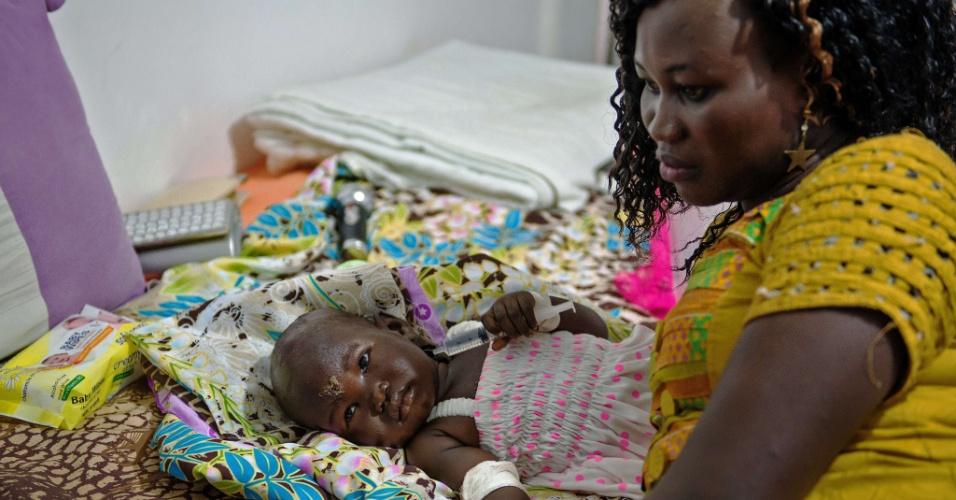5.nov.2015 - A bebê Nyloak Thong, de 13 meses, recebe atendimento médico em hospital após sobreviver à queda de um avião próximo à capital do Sudão do Sul, Juba, ao lado de Achol Deng, jornalista que diz ter ajudado a resgatá-la