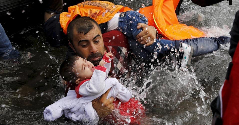 24.set.2015 - Refugiado sírio segura seus filhos no esforço para andar fora de um bote na ilha de Lesbos, depois de atravessar uma parte do Mar Egeu da Turquia para Grécia