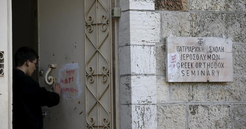 """17.jan.2016 - Um monge apaga pichação feita na Abadia da Dormição, localizada nos arredores da velha cidade amuralhada de Jerusalém. O local amanheceu, neste domingo, com pichações contra os cristãos, informou a polícia, que abriu uma investigação. O vandalismo no edifício, que pertence a uma ordem beneditina alemã, diz: """"morte aos pagãos cristãos, inimigos de Israel"""", """"Seja seu nome apagado"""" e """"Para os cristãos o inferno"""""""