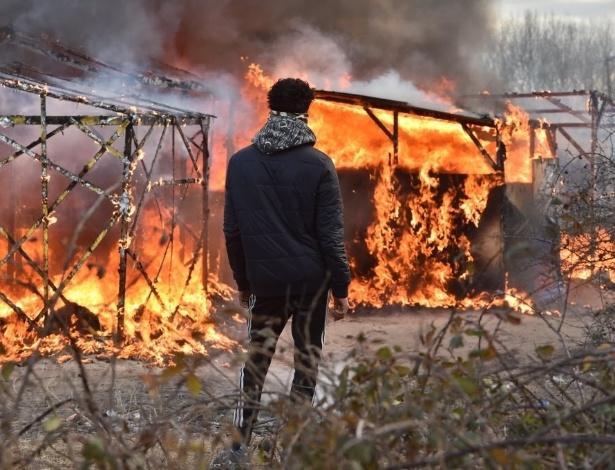 """29.fev.2016 - Imigrante observa acampamento em chamas em Calais (França). A Justiça autorizou a retirada de imigrantes do local conhecido como """"Selva"""", na cidade portuária"""
