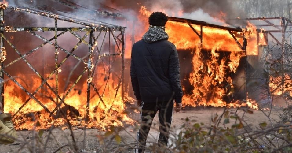 """29.fev.2016 - Imigrante observa acampamento em chamas na cidade Calais, na França. Um tribunal francês autorizou a retirada de centenas de imigrantes da cidade portuária. Os refugiados instalados na """"selva"""", procedentes em sua maioria de Síria, Afeganistão e Sudão, querem viajar à Inglaterra e muitos tentam fazê-lo embarcando clandestinamente em caminhões que circulam entre os dois países"""