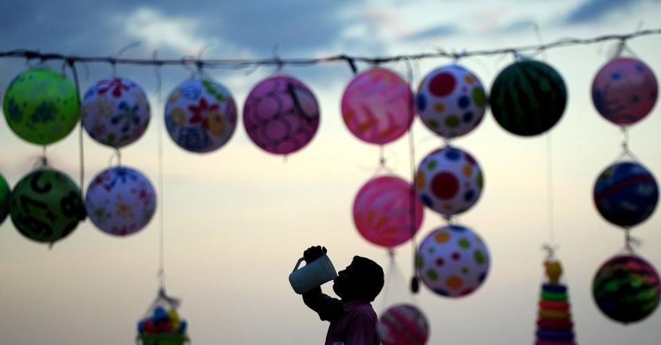 22.set.2016 - Vendedor bebe água junto a bolas de plástico expotas para venda na praia de Marina, em Chennai (Índia)