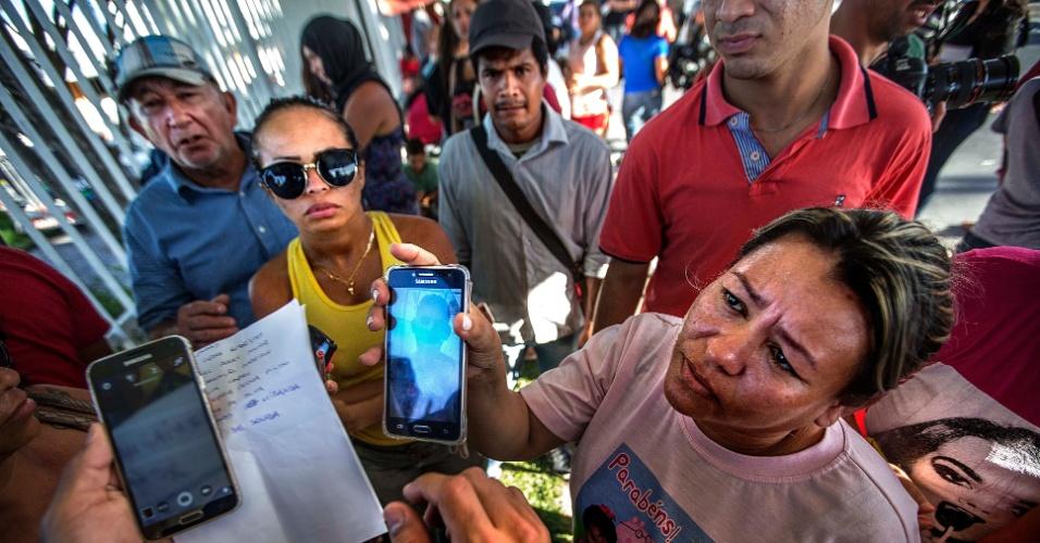 3.jan.2017 - Porta do Instituto Medico Legalde Manaus, onde familiares de presos mortos no presídio da cidade esperam para saber se seu parente esta morto e mostram fotos deles em celulares