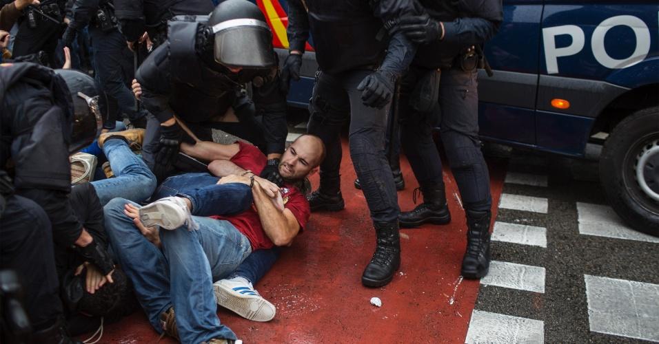 1º.out.2017 - Policiais espanhóis entram em confronto com manifestantes em frente a um local de votação em Barcelona