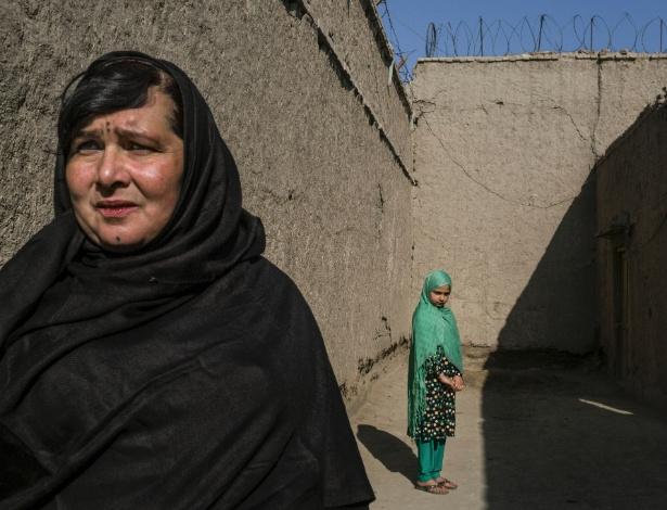 Meena, 11, ao lado de sua mãe Shirin Gul, uma serial killer que está cumprindo prisão perpétua, em Jalalabad, no Afeganistão