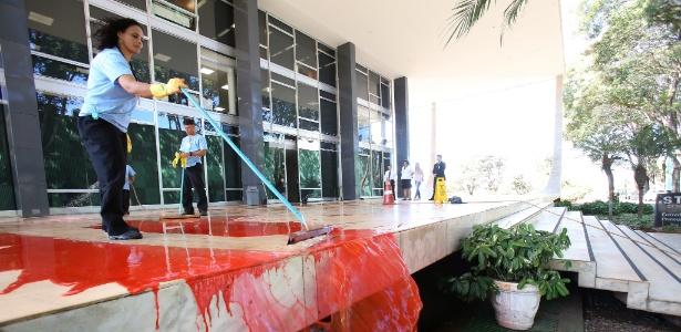 Funcionários limpam tinta vermelha jogada por manifestantes na entrada do STF - Dida Sampaio/Estadão Conteúdo