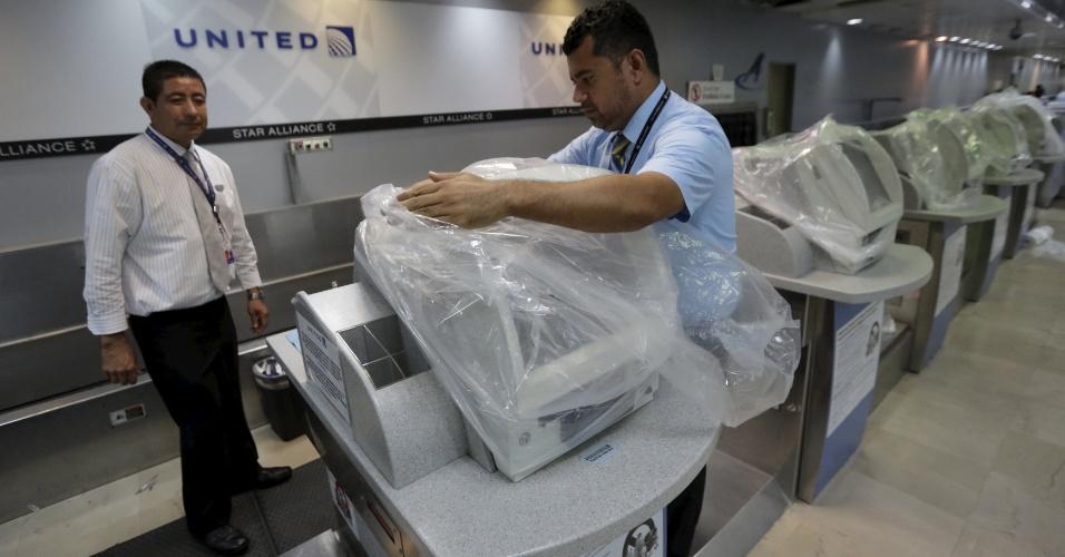 23.out.2015 - Funcionários da companhia aérea americana United Airlines cobrem computadores no aeroporto internacional de Puerto Vallarta, no México, diante da aproximação do furacão Patricia