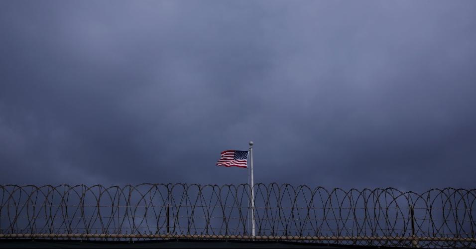 28.mar.2016 - O centro se tornou alvo de denúncias de violações de direitos humanos e fechar a prisão era uma das promessas de campanha de Obama em 2008, mas problemas jurídicos e políticos e entraves sobre o destino dos detidos o impediram de cumpri-la até agora. Na imagem feita no dia 22 de março, a bandeira dos Estados Unidos aparece hasteada no acampamento da Força Tarefa Conjunta de Guantánamo, na base Naval norte-americana em Cuba