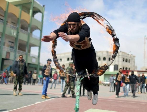 28.mar.2016 - Um estudante palestino salta através de um anel de fogo durante um show de estilo militar em uma escola em Rafah, na faixa de Gaza