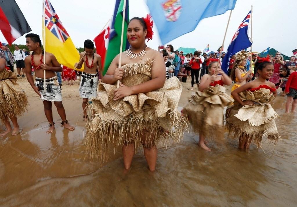 8.mai.2016 - Mulheres e meninas das ilhas do Pacífico entram na água no porto de Newcastle Harbour e assistem uma frota de embarcações sair deixar o cais