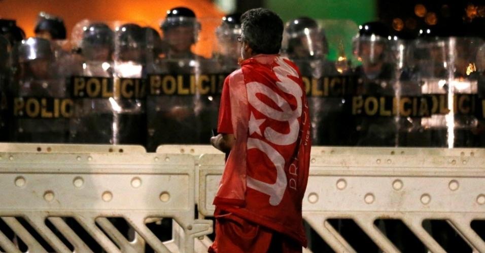 11.mai.2016 - Enrolado em bandeira com o nome da presidente, manifestante contrário ao impeachment de Dilma Rousseff (PT) observa barricada da polícia em Brasília (DF), enquanto senadores discutem admissibilidade do processo