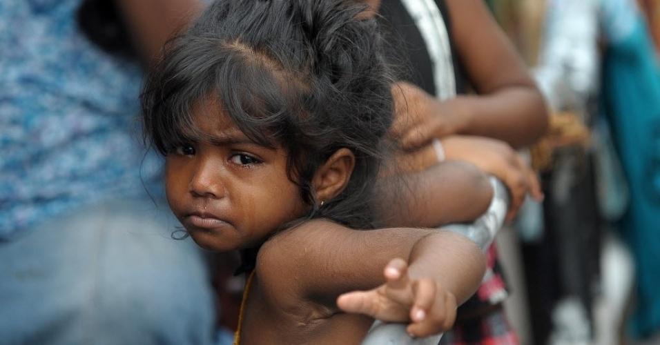 22.mai.2016 - Vítima das enchentes que atingiram o Sri Lanka nos últimos dias, menina espera por mantimentos neste domingo, perto da capital, Colombo. Mais de 80 pessoas morreram e outras 118 estão desaparecidas