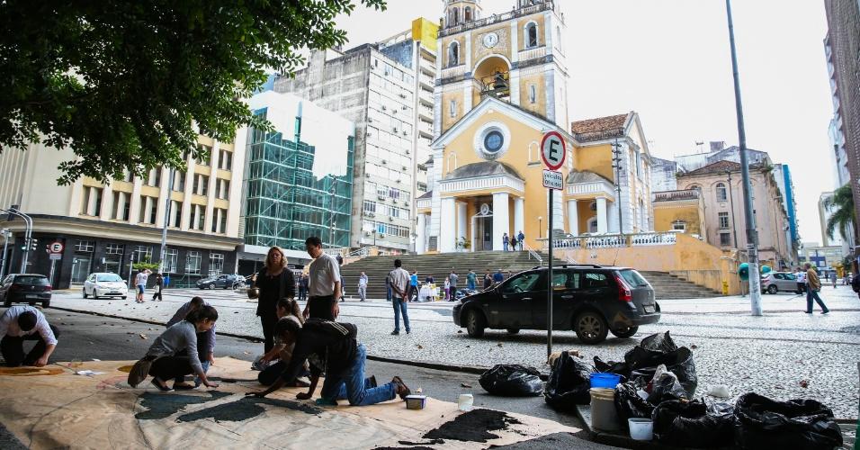 26.mai.2016 - Fiéis montam tapetes de Corpus Christi em frente à catedral, no centro de Florianópolis. Eles usam serragem, flores, pó de café, sal e materiais reciclados para montar os tapetes, usados na passagem das procissões que marcam a data