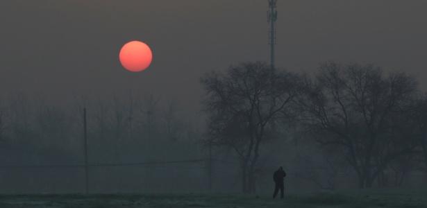 Homem anda durante o nascer do sol com poluição atmosférica em dia com alerta vermelho emitido para a poluição do ar em Pequim, na China
