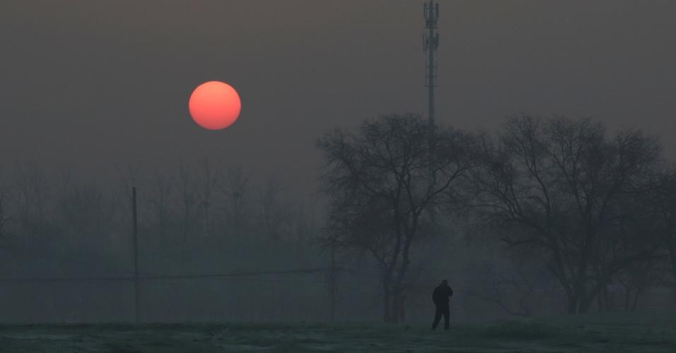 19.dez.2016 - Homem anda durante o nascer do sol com poluição atmosférica em dia com alerta vermelho emitido para a poluição do ar em Pequim, na China