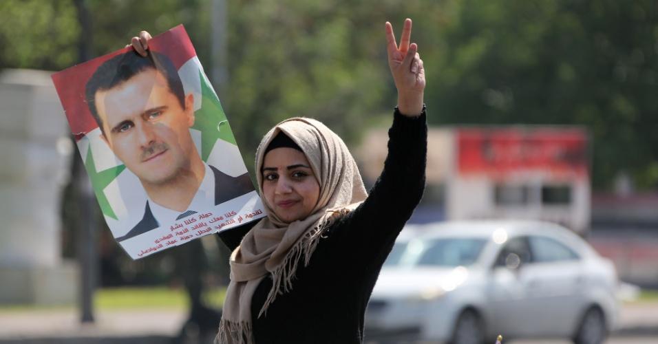 14.abr.2018 - Mulher carrega retrato do presidente Bashar al-Assad durante protesto em Damasco contra os ataques contra a Síria