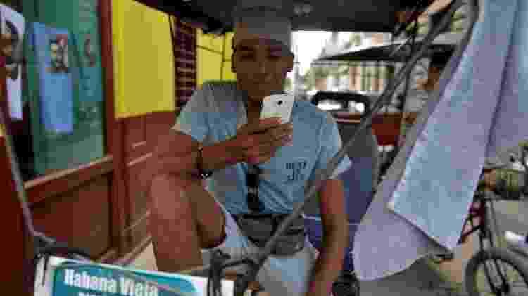 Homem usa a internet no seu celular em Havana no dia em que Cuba liberou o acesso completo ao serviço, no começo de dezembro - Yamil Lage/AFP - Yamil Lage/AFP