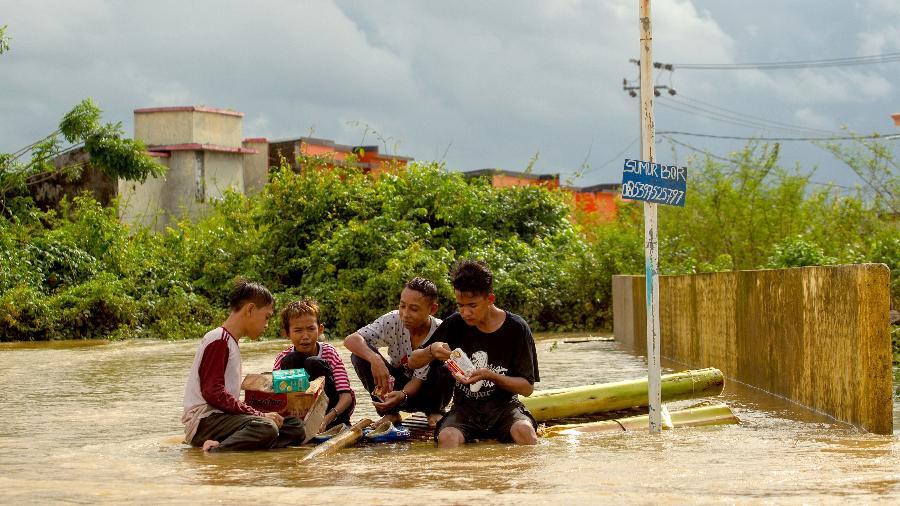 24.jan.2019 - Grupo de jovens indonésios almoça sobre as águas da enchente que atinge a cidade de Makassar  - Yusuf Wahil/AFP