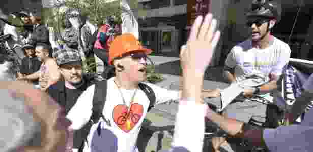 Ciclista puxa faixa de integrantes do Movimento Brasil Livre, que protestavam contra o PT, durante inauguração da ciclovia da avenida Paulista - Guga Gerchmann/Eleven/Agência O Globo