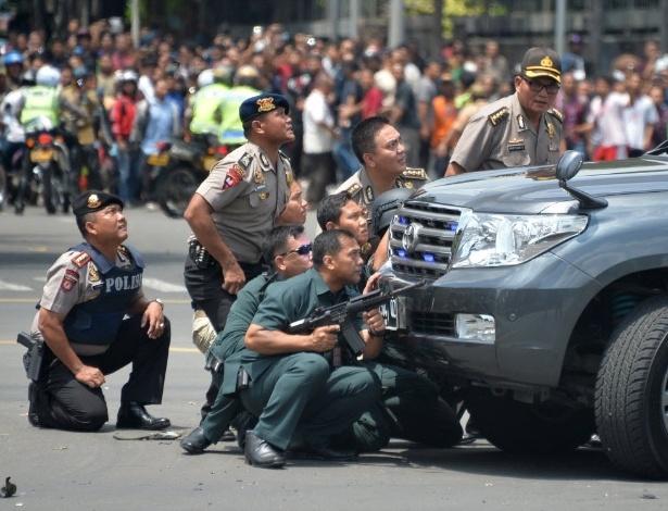 14.jan.2016 - Policiais indonésios se protegem contra explosivos ao se aproximarem de local atingido por bomba após uma série de explosões no centro de Jacarta. Uma série de explosões e um tiroteio deixou, ao menos sete mortos. A polícia detalhou que o ataque foi cometido por entre 10 e 14 homens armados e que ao menos cinco deles foram mortos ou se explodiram