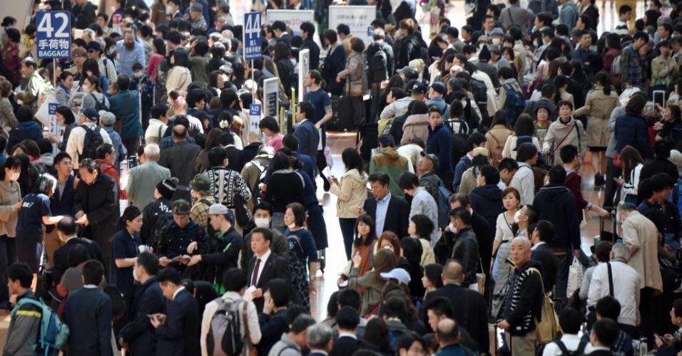 22.mar.2016 - Terminal do aeroporto de Haneda, em Tóquio, fica lotado de passageiros tentando fazer check in ou comprar tickets. Uma falha eletrônica fez com que a companhia All Nippon Airways cancelasse mais de cem voos domésticos, afetando milhares de passageiros, de acordo com a companhia