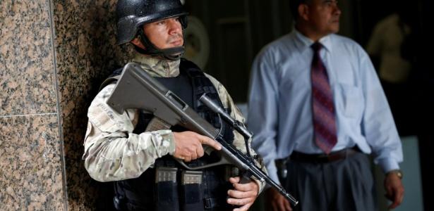 Oficial da Força Especial da Venezuela monitora saída do Banco Central do país após homem armado invadir o local