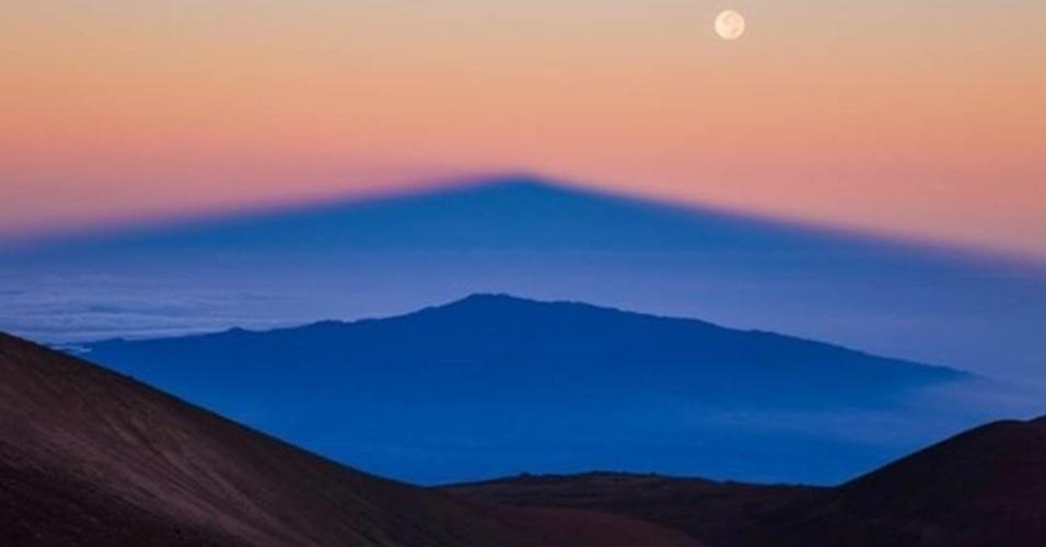 1º.ago.2016 - A sombra do vulcão Mauna Kea, no Havaí, é projetada pelo Sol nascente sobre outro vulcão, Hualalai, enquanto a Lua cheia brilha no céu, nesta imagem de Sean Goebel