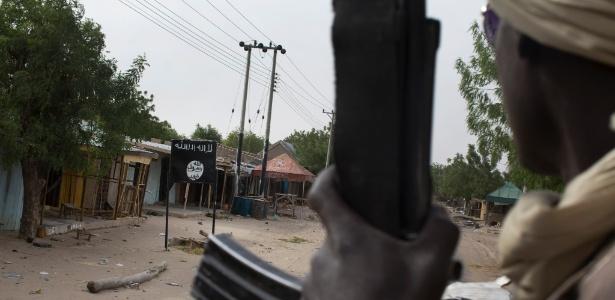 Soldado do Chade passa diante de local com a bandeira do Boko Haram