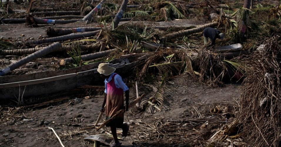 9.out.2016- Mulher caminha entre árvores caídas em Coteaux, Haiti, após passagem do furacão Matthew