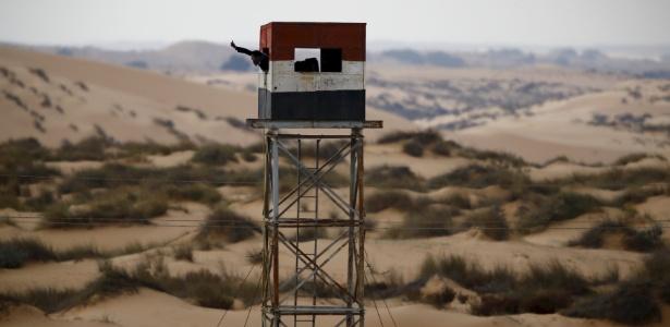 10.fev.2016 - Policial egipcio acena de uma torre de observação na fronteira com Israel na península do Sinai