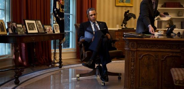 Barack Obama lê em seu iPad no Salão Oval da Casa Branca, em Washington