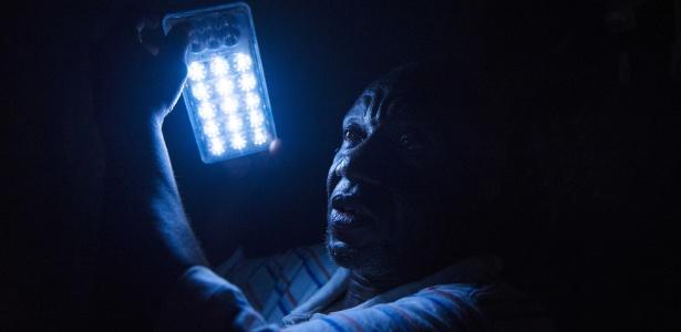 Hayes Lewis em sua casa com uma luz de lanterna que funciona a bateria, em Sayon Town, Libéria