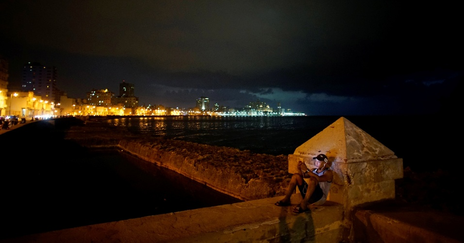Jovem usa celular para conectar-se à internet, na praia de Malecón, em Havana