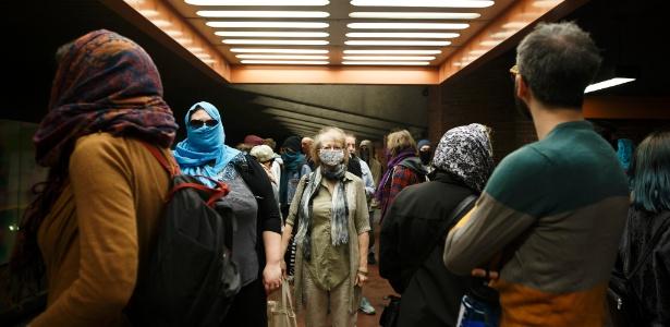 Manifestantes aguardam trem no metrô de Montreal com os rostos cobertos para mostrar sua objeção à nova lei que proíbe o uso de veú para pessoas que utilizam serviços públicos na província, em Montreal, Canadá