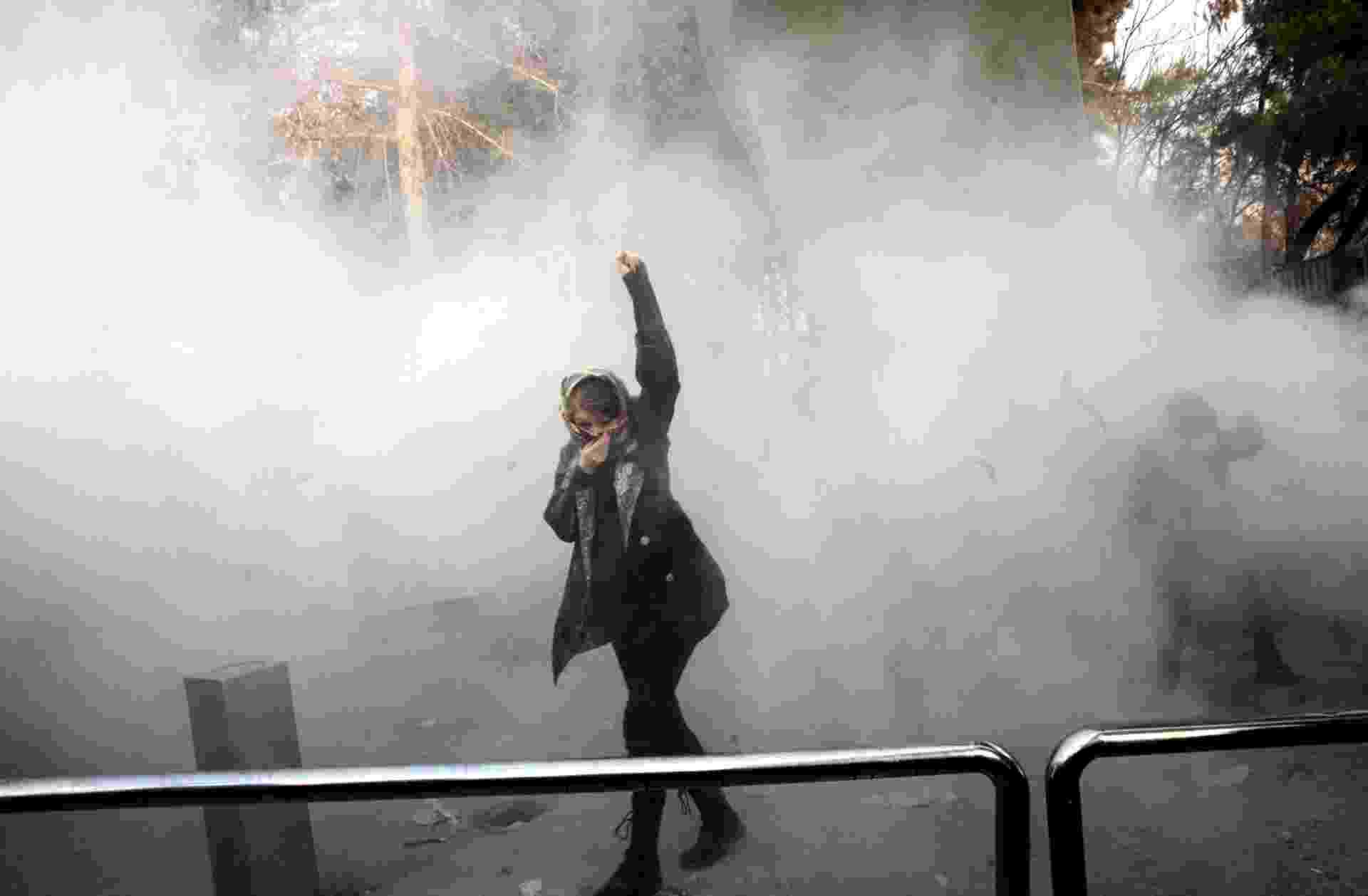 Uma mulher iraniana caminha em meio à fumaça de gás lacrimogêneo na Universidade de Teerã durante protesto impulsionado pela raiva sobre os problemas econômicos, na capital Teerã, em 30 de dezembro de 2017 - AFP